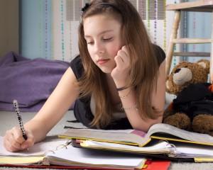 Cute young teenage girl doing homework in her bedroom